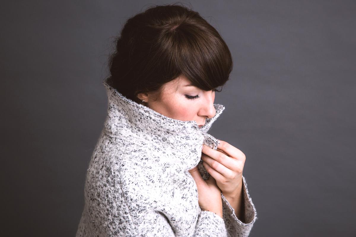 Woman in a coat against grey healing fertility