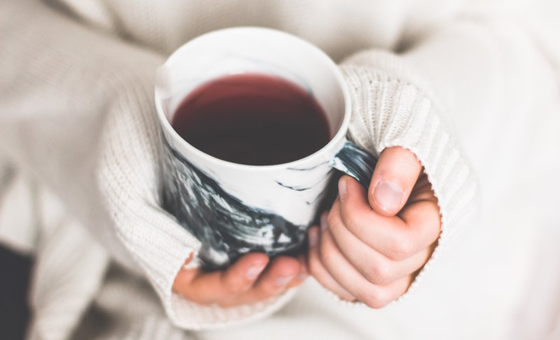 holding a cup of warming tea of spices