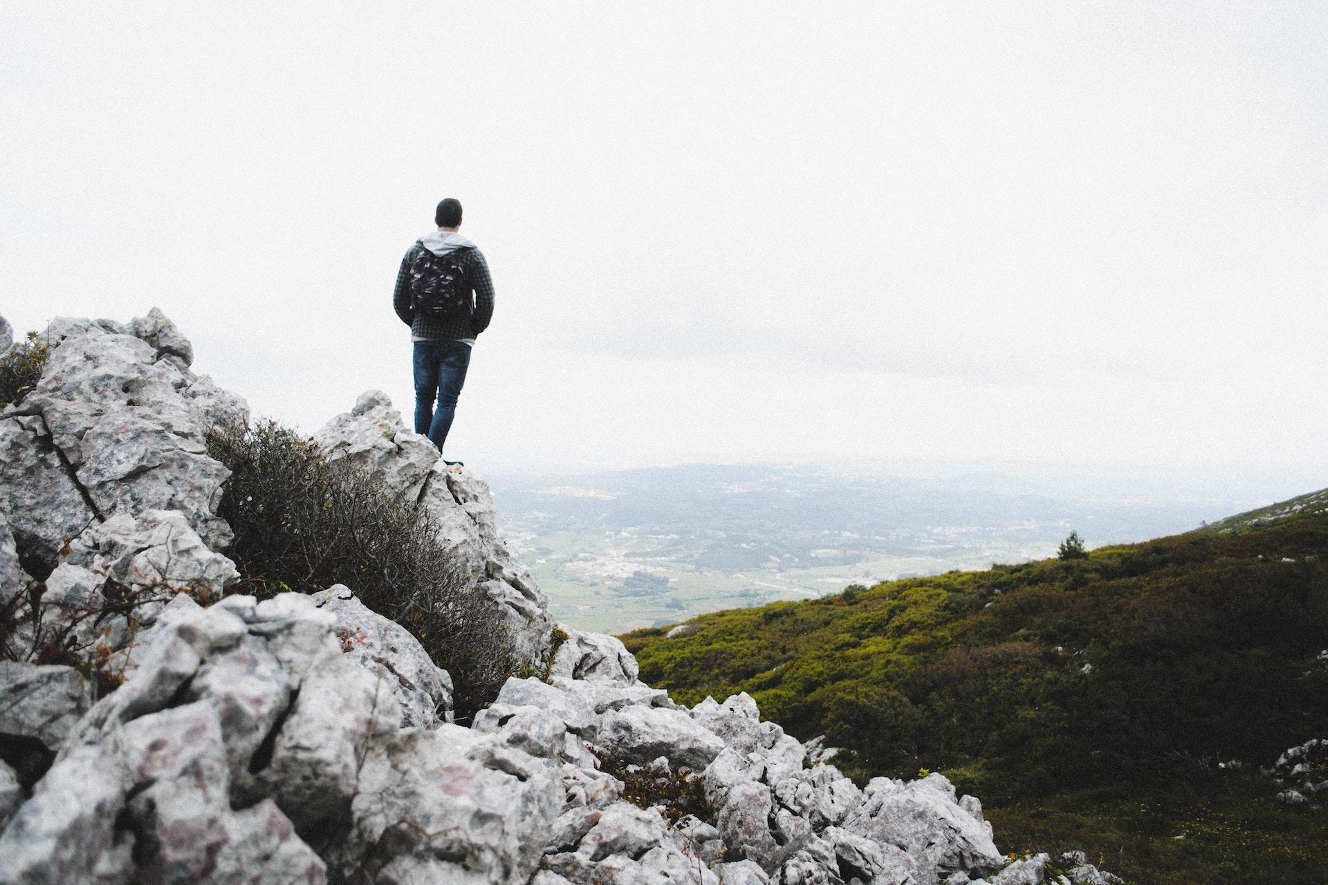 man standing on a peak