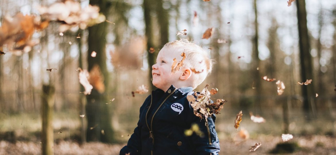 young boy laughing under falling leaves autumn perfectionism