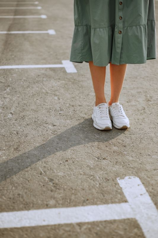 girl in a green skirt standing in white sneakers